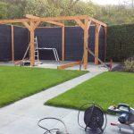 Overkapping in tuin met zwarte achterwanden